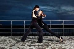 Danse de salon supérieure de couples sur le coucher du soleil foncé Image libre de droits