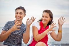 Danse de sourire d'homme et de femme se reposant sur la plage Photographie stock libre de droits