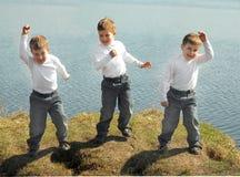 Danse de trois garçons sur l'herbe verte Image stock