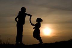 Danse des enfants dans le coucher du soleil Photos stock