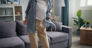 Danse drôle de chant de fille écoutant la musique dans des écouteurs tenant le smartphone clips vidéos