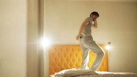 Danse drôle de jeune homme sur le lit le soir avant le sommeil banque de vidéos