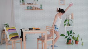 Danse drôle de jeune femme dans des pyjamas de port de cuisine pendant le matin La fille de brune dans l'humeur gaie écoute musiq image stock