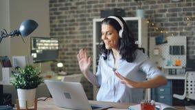 Danse espiègle de fille mettant en oeuvre la musique dans des écouteurs et à l'aide de l'ordinateur portable dans le bureau banque de vidéos