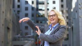 Danse femelle comblée de directeur en dehors de l'immeuble de bureaux, célébrant la promotion clips vidéos