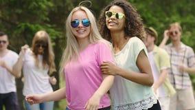 Danse gaie de bande de filles devant l'appareil-photo à l'exposition de talent, flirt, souriant clips vidéos
