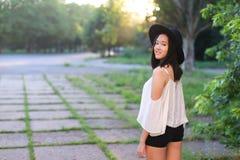Danse gaie de rire d'émotions de coucher du soleil asiatique femelle merveilleux de chapeau image libre de droits