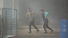 Danse habile de deux jeune danseurs d'amis dans la salle sombre et poussiéreuse du bâtiment abandonné Les types entreprenant des  banque de vidéos