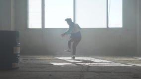 Danse habile de jeune homme dans un b?timent abandonn? Culture d'houblon de hanche r?p?tition contemporain banque de vidéos