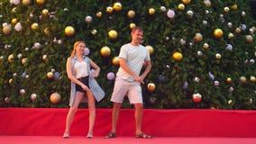 Danse heureuse d'homme et de femme de couples sur le fond de l'arbre de Noël dans une ville tropicale Le concept de la nouvelle a banque de vidéos