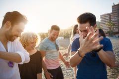 Danse heureuse d'homme sur la plage avec des amis battant ses mains Photographie stock
