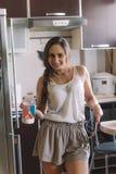 Danse heureuse de femme avec le smartphone et la bouteille de lait photographie stock libre de droits