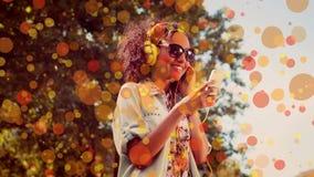 Danse heureuse de femme de métis tandis qu'elle est grâce de écoute de musique à ses écouteurs banque de vidéos