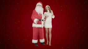 Danse heureuse de fille de sourire de Noël avec Santa Claus sur le fond rouge avec la neige photographie stock libre de droits