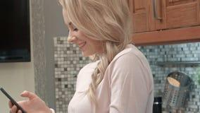 Danse heureuse de jeune femme dans la cuisine écoutant la musique sur le smartphone et le café à la maison Photos stock