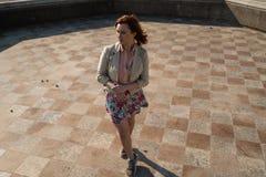 Danse heureuse de jeune femme dans une fontaine vide utilisant une jupe colorée photographie stock libre de droits