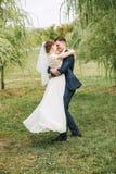 Danse heureuse de ménages mariés sur la nature parmi des saules Photo stock