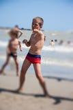 Danse heureuse de petit garçon sur la plage au temps de jour Photo stock