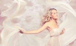Danse insouciante de belle femme heureuse avec le tissu de vol Photographie stock
