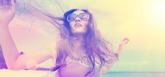 Danse insouciante de jeune femme dans le coucher du soleil sur la plage photographie stock libre de droits