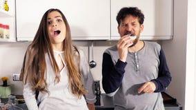 Danse maladroite de couples dans la cuisine mangeant le beignet faisant l'expression drôle de visages banque de vidéos