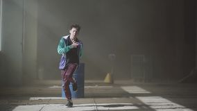 Danse masculine de danseur de jeune hip-hop asiatique dans le bâtiment abandonné foncé devant le baril de gaz bleu contemporain g banque de vidéos