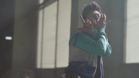 Danse masculine de danseur de jeune hip-hop asiatique de portrait dans le bâtiment abandonné foncé devant le baril de gaz bleu Le clips vidéos