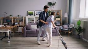 Danse nettoyante à l'aspirateur de plancher de mari et d'épouse ayant l'amusement en appartement moderne banque de vidéos