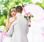 Danse romantique de couples de nouveaux mariés heureux au bas-côté de mariage avec les décorations et les fleurs roses Image libre de droits