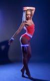 Danse sensuelle de fille dans le costume rougeoyant Photographie stock libre de droits