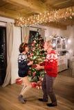 Danse supérieure de couples par l'arbre de Noël le soir Images stock