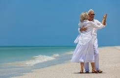 Danse supérieure heureuse de couples retenant des mains sur une plage tropicale Image libre de droits