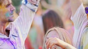 Dansend die paar in poeder wordt gekleurd die video op smartphone schieten bij Holi-festival stock videobeelden