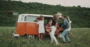 Dansend paar in het midden van aard, het bewegende verbazen, iemand die bij de gitaar spelen, die in de retro bestelwagen zitten  stock videobeelden
