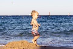 Dansende peuterjongen op de strand aganst overzeese mening Royalty-vrije Stock Afbeeldingen