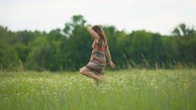 Dansende vrouw op de zomergebied, vrouwelijk blootvoets op de groene bewegingen van de grasdans stock footage