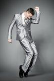 Dansende zakenman in elegant grijs kostuum. Stock Foto