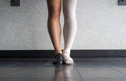 Danser zich in parallelle positie bij de staaf bevinden, halve kleding in de kledij van de Jazzdans en de helft die in balletkled Stock Fotografie