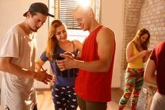 Dansers op pauze van dansen die op celtelefoon kijken stock foto