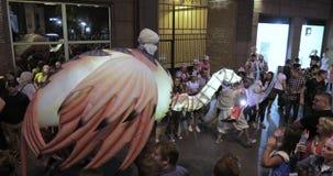 Dansers op stelten in kostuums van grote vogels en met equestrians in tulbanden en pelgrims met slagwerkers stock video