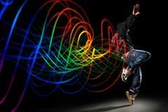 Danseur avec des ondes de lumière au-dessus de fond noir Image libre de droits