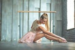 Danseur classique attirant s'asseyant sur le plancher photo stock
