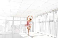 Danseur classique féminin élégant dans le tutu rose pratiquant et souriant photographie stock libre de droits