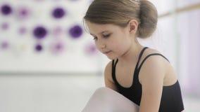 Danseur classique mignon attachant des chaussures de ballet avant la formation clips vidéos