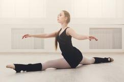 Danseur classique classique s'étirant dans le cours de formation blanc Images stock