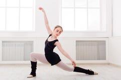Danseur classique classique s'étirant dans le cours de formation blanc Photographie stock