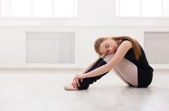 Danseur classique classique s'asseyant dans le cours de formation blanc Photos stock