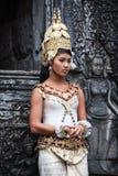 Danseur d'apsara de Khmer à côté de la statue en pierre de danseur Photographie stock