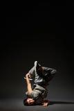 Danseur de hip-hop posant au-dessus de l'obscurité Images stock