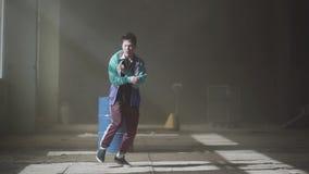 Danseur masculin de jeune hip-hop asiatique dans la danse d'usage de sport dans le bâtiment abandonné foncé devant le baril de ga banque de vidéos